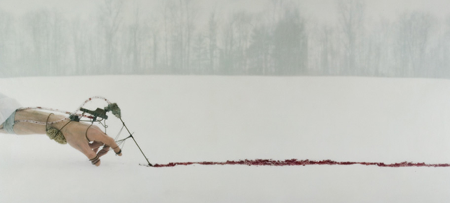 human hand with device drawing a line in blood on snow