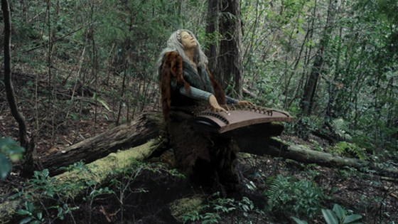 woman playing a harp in a woodland