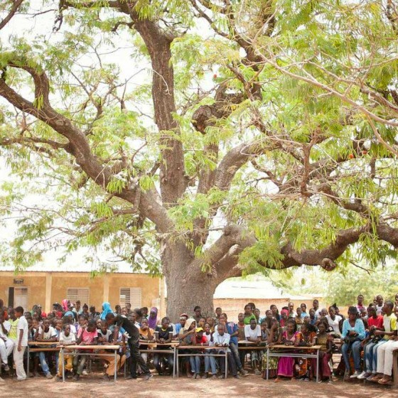 teachers and students from Senegal sitting in front of school