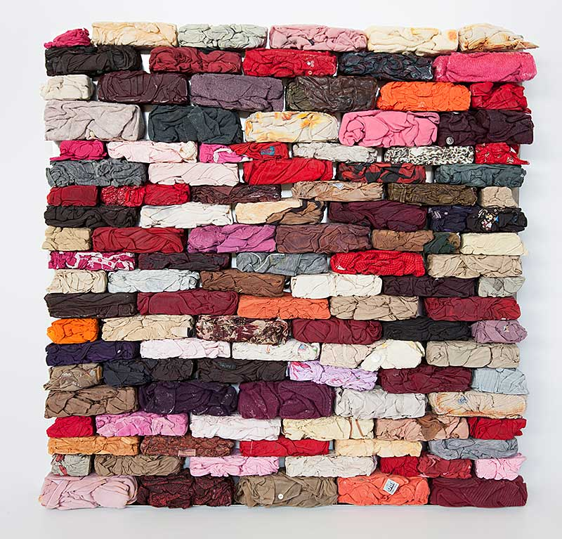 sculpture in form of brick wall made from discarded textiles