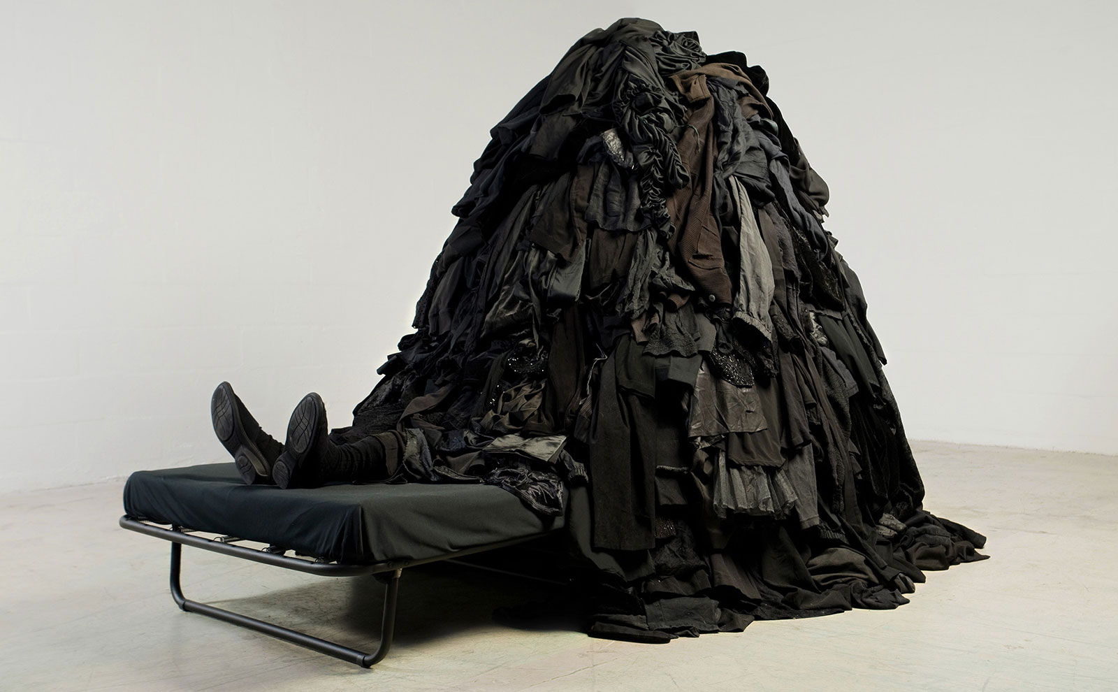 figurative sculpture under pile of discarded textiles