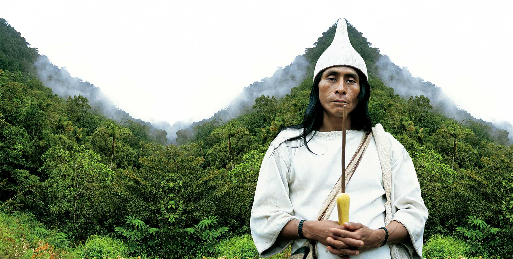 indigenous man in front of forested mountains