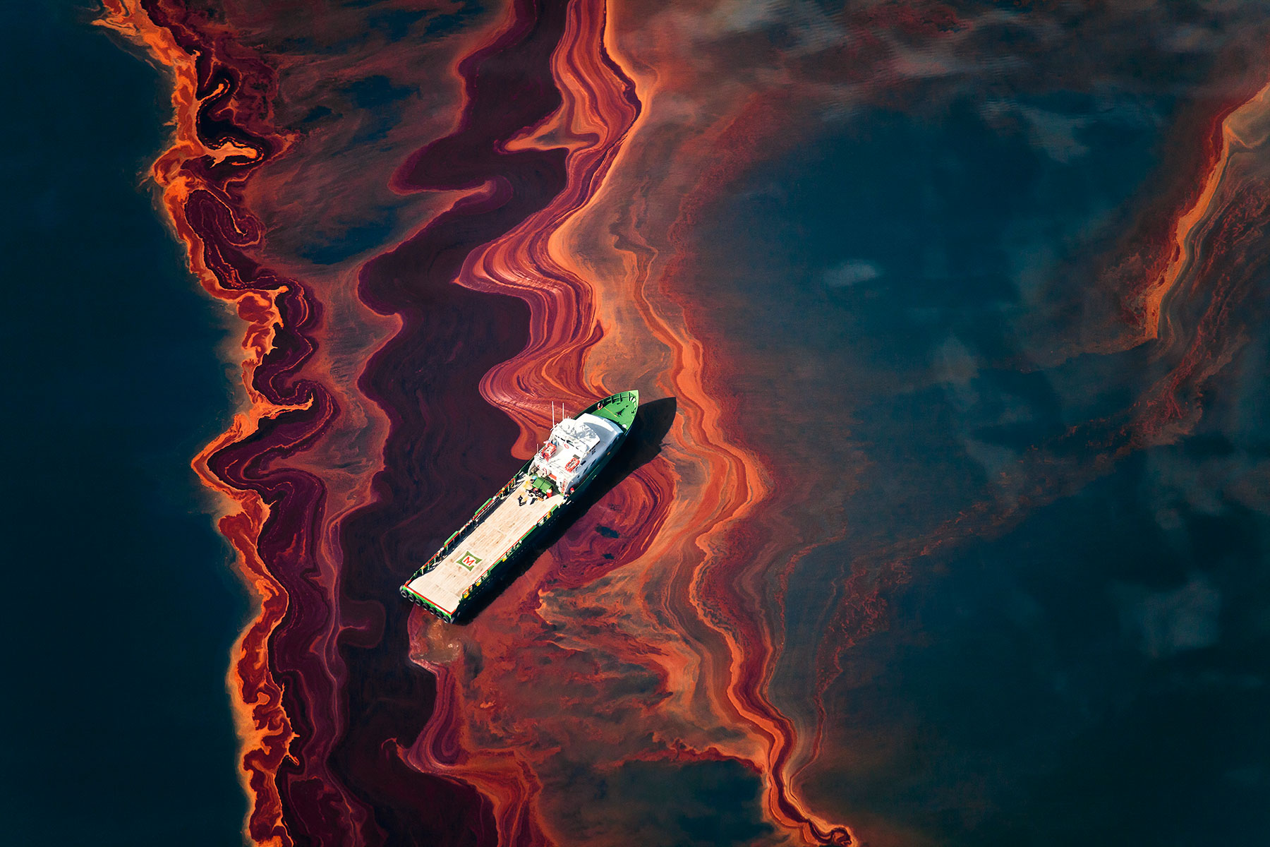 boat and oil slick in body of water