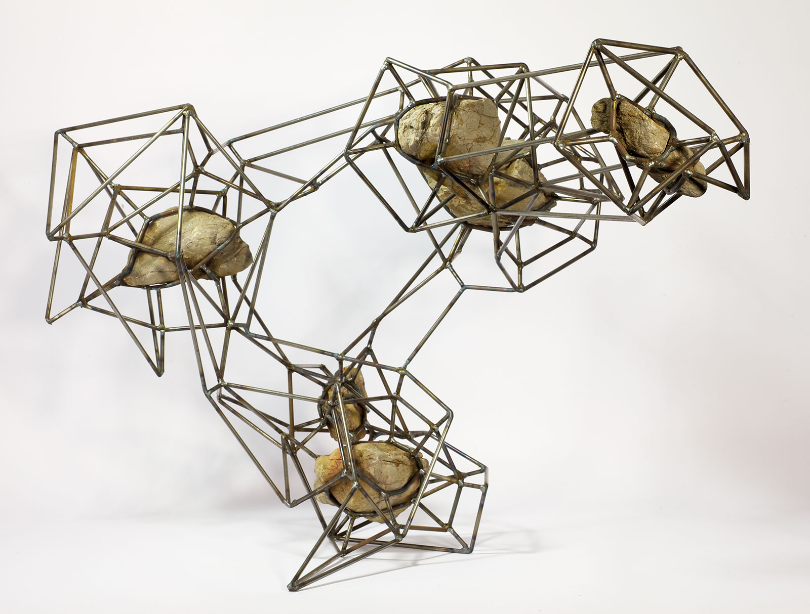 rocks suspended in steel lattice