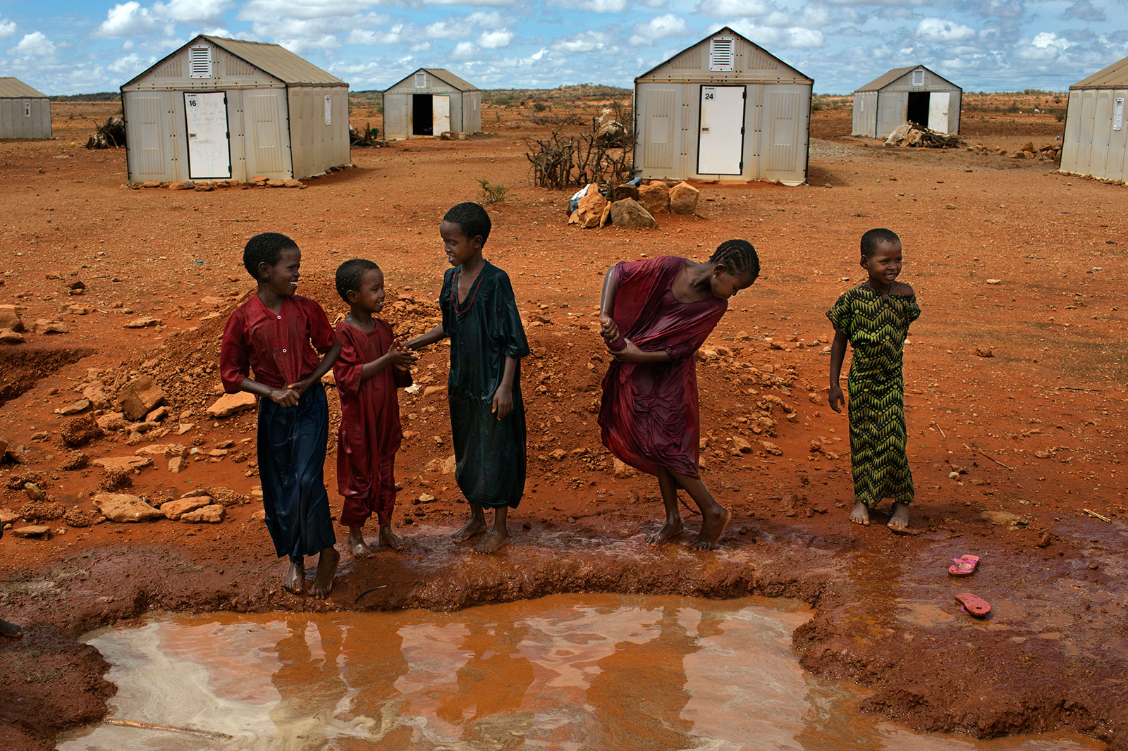 African children in front of temporary housing