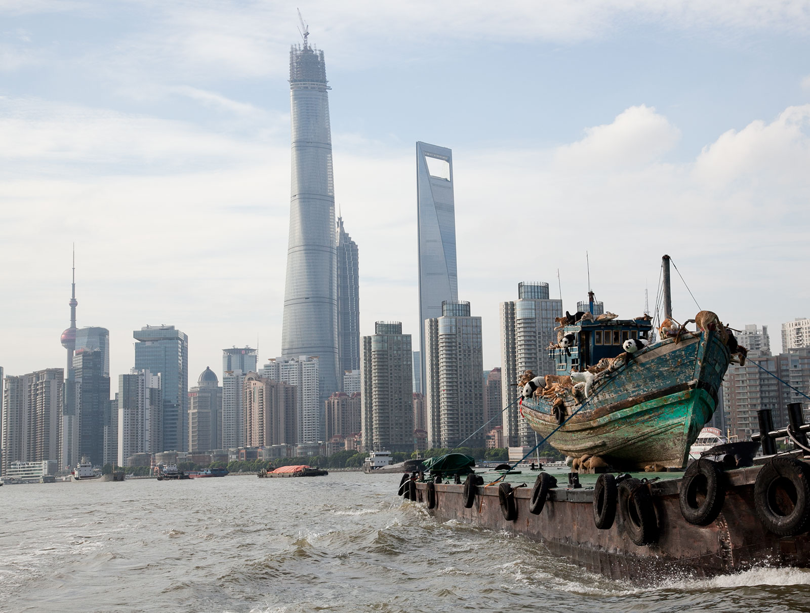 fishing boat with wildlife replicas floating toward city